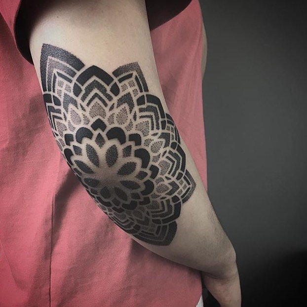 Dot work mandala tattoo on the elbow