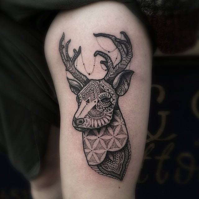 Black deer tattoo on the thigh