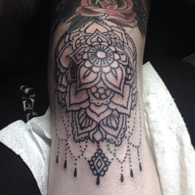 Black mandala tattoo on the knee