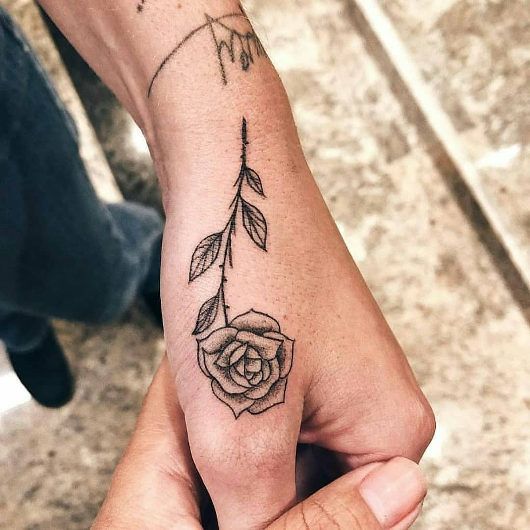 Black rose tattoo on the thumb