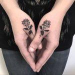 Black rose tattoos on thumbs