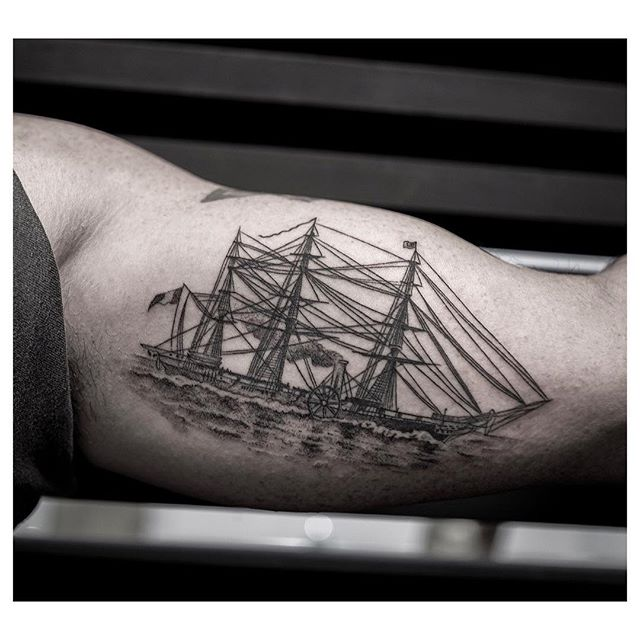 Black ship tattoo on the bicep