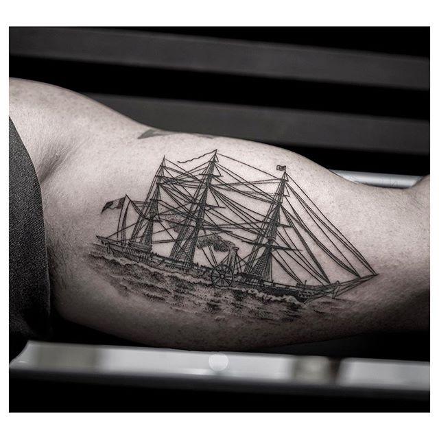 Black ship tattoo on the bicep