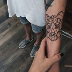 Geometric wolf head tattoo on the inner arm