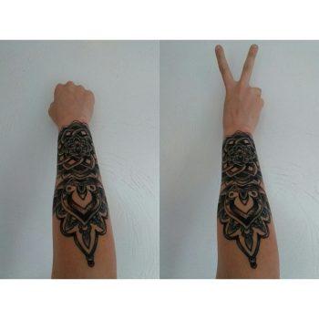 Large black mandala tattoo on the arm