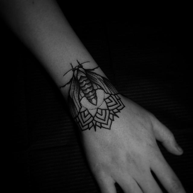 Mandala and bug tattoo on the wrist