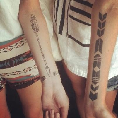 Matching arrow tattoos on arms