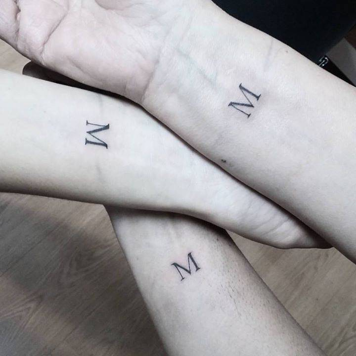 Matching letter M tattoos