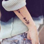 Minimal arrow tattoo on the forearm