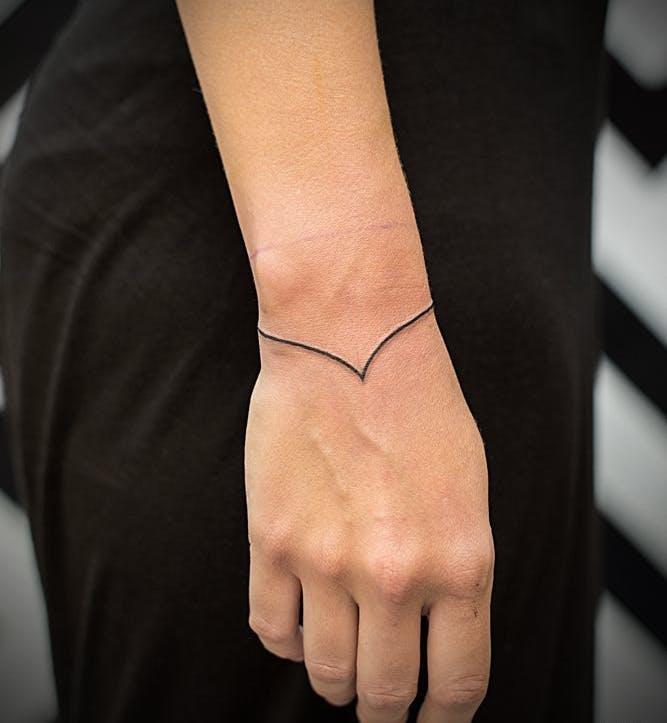 Minimal black line wristband tattoo