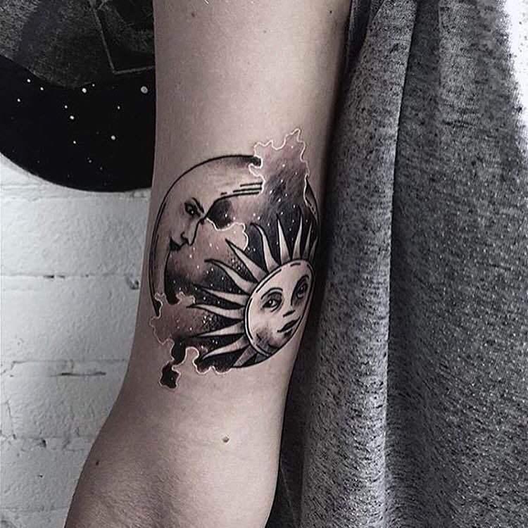 Moon and sun circular tattoo on the inner arm