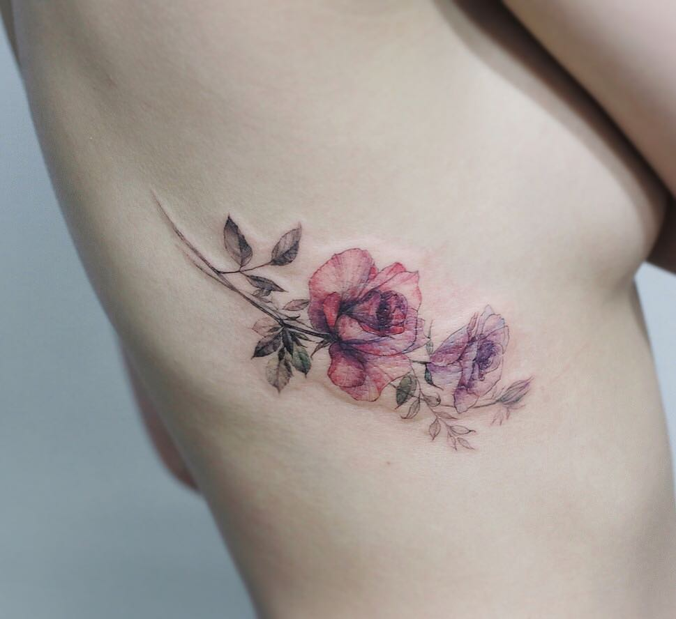 Subtle wildflower tattoo on the rib cage