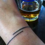Thin black line tattoo on the wrist