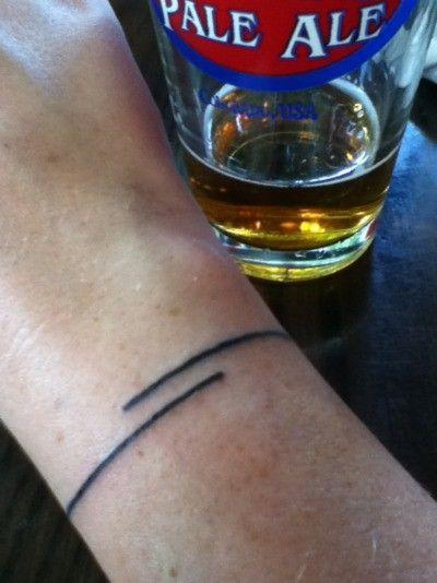 Thin black line tattoo on the wrist