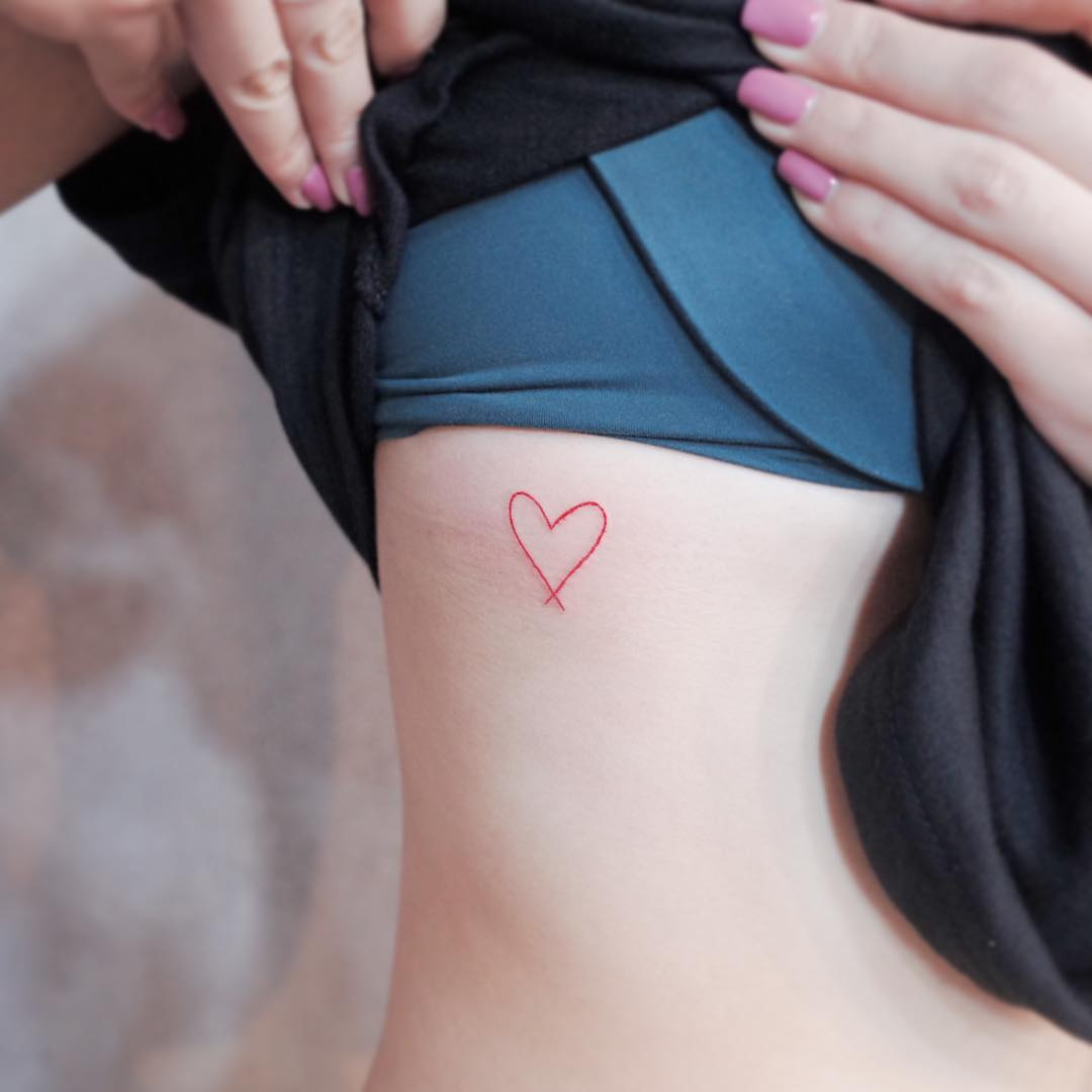 Tiny red heart tattoo on the rib cage