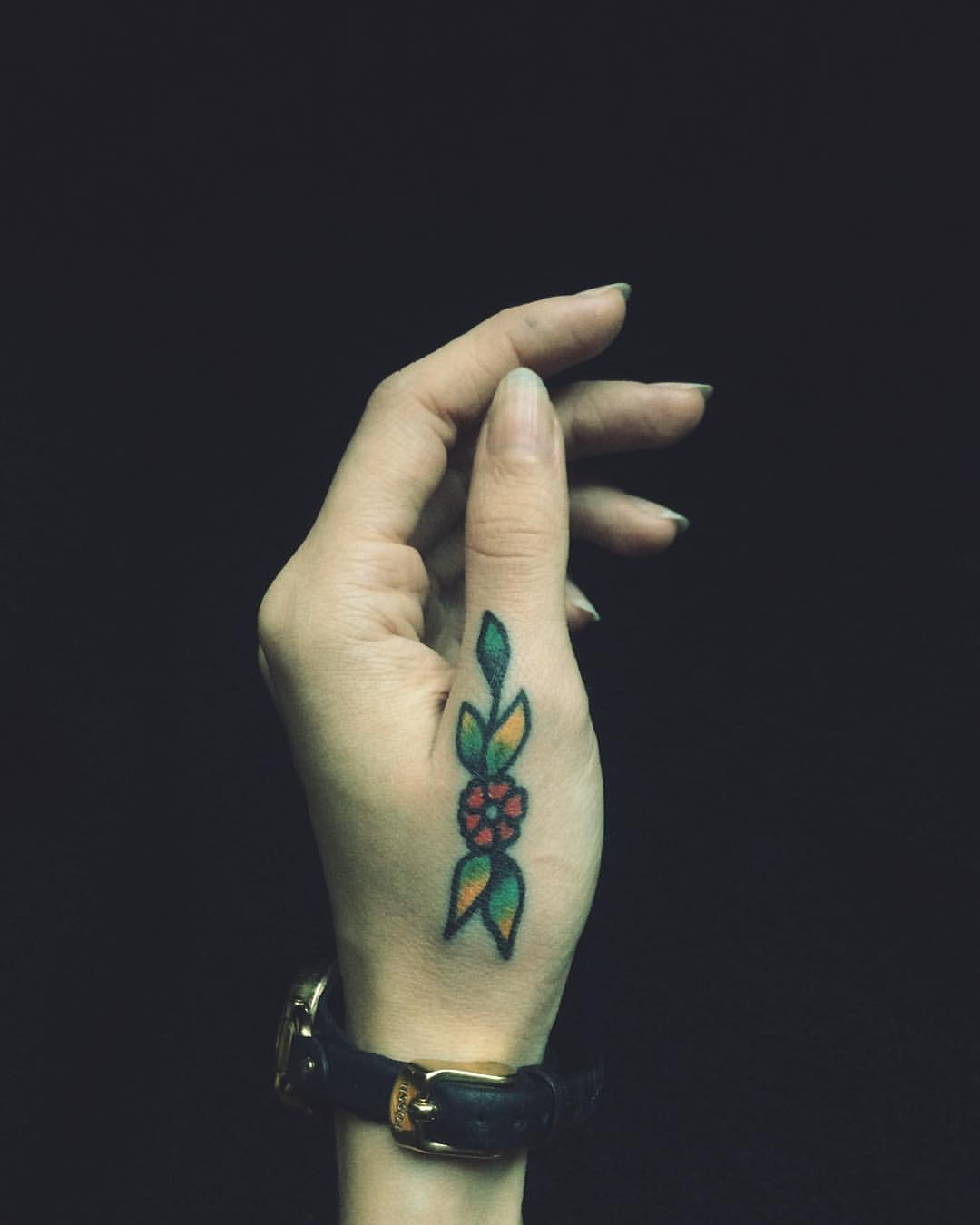 Traditional flower tattoo on a thumb