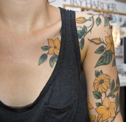 Yellow flower tattoo on the shoulder and sleeve