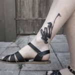 Abstract black paintbrush ankle tattoo