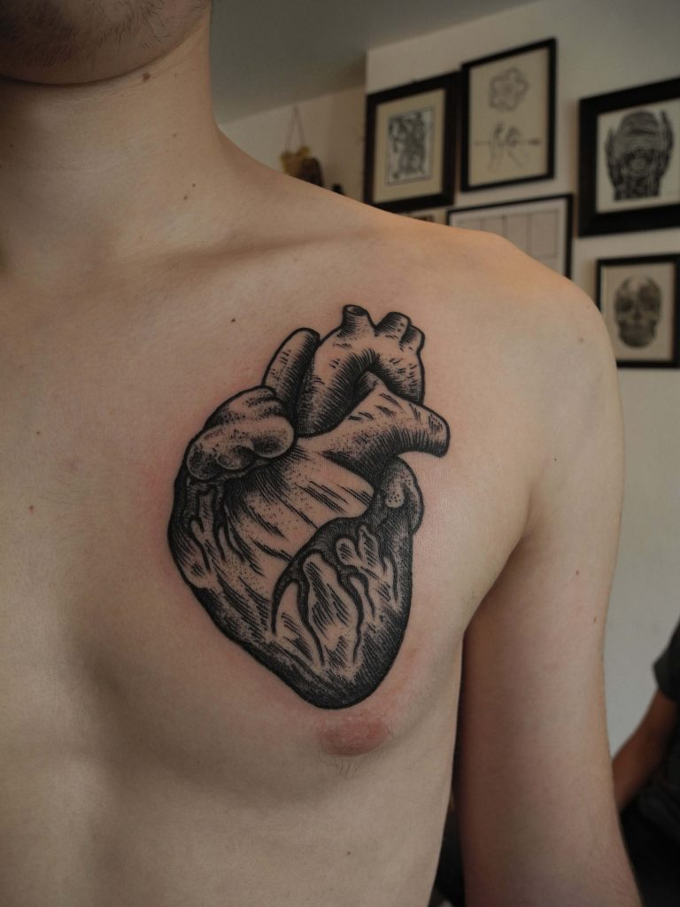 Black anatomical heart tattoo on the chest
