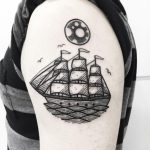 Black circular tattoo of a sailing vessel