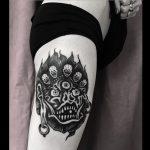 Black devil tattoo on the tricep