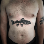 Black fish tattoo on the belly