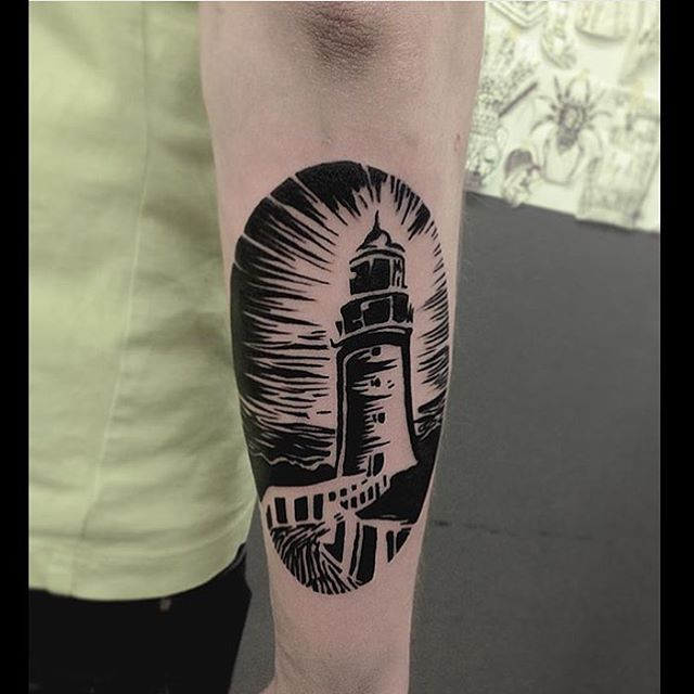Black lighthouse tattoo on the forearm