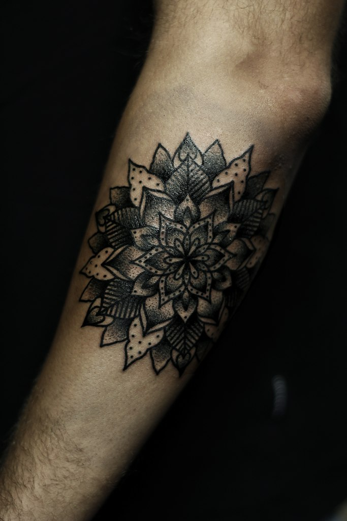 Black mandala tattoo on the left forearm