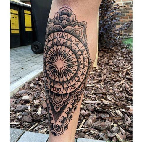 Black mandala tattoo on the right shin