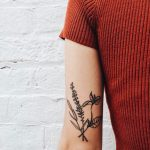 Black minimal flower tattoo on the inner arm