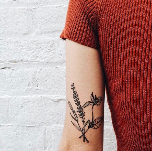 Black minimal flower tattoo on the inner arm