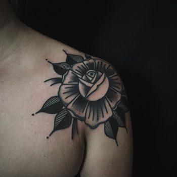 Black rose tattoo on the shoulder