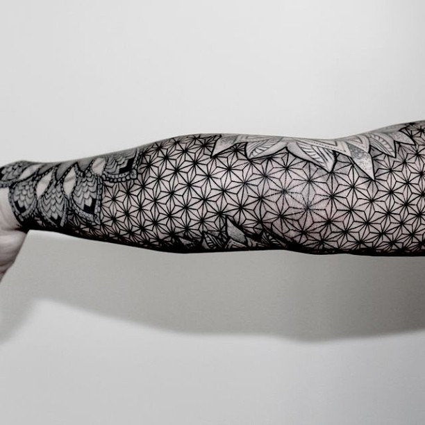 Black sacred geometry tattoo on the arm
