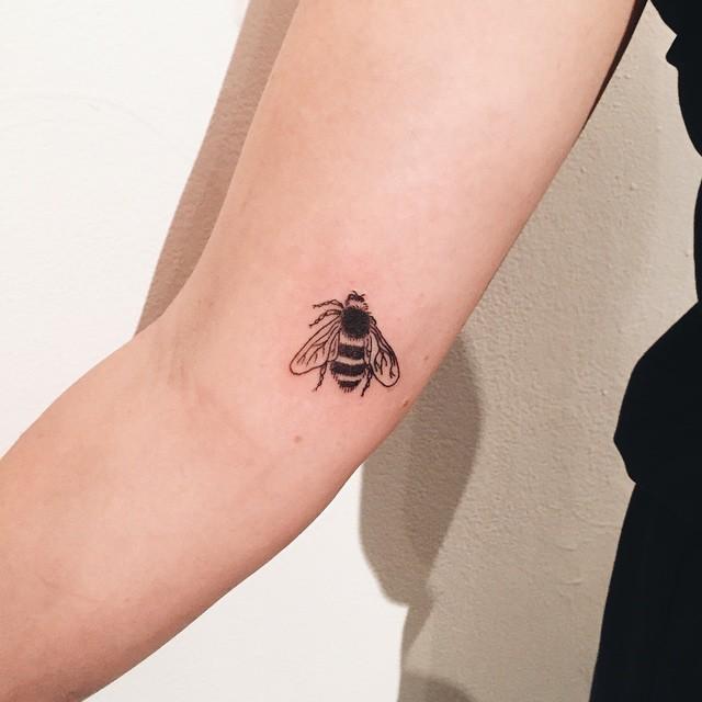 Black small bee tattoo