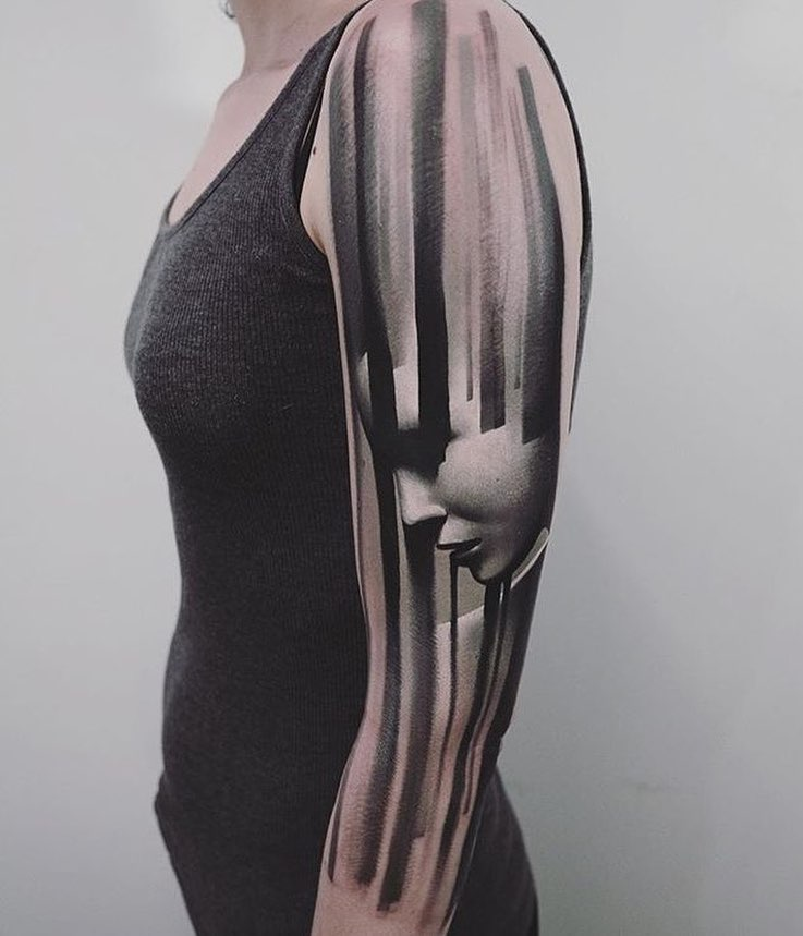 Black stripes and face tattoo on the sleeve