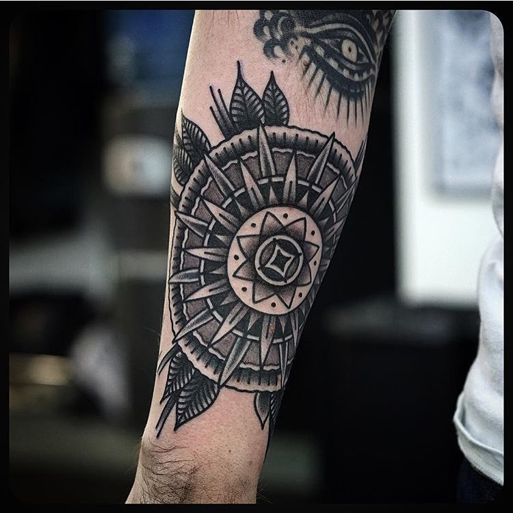 Black traditional mandala tattoo on the arm