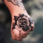 Black traditional rose tattoo on the hand