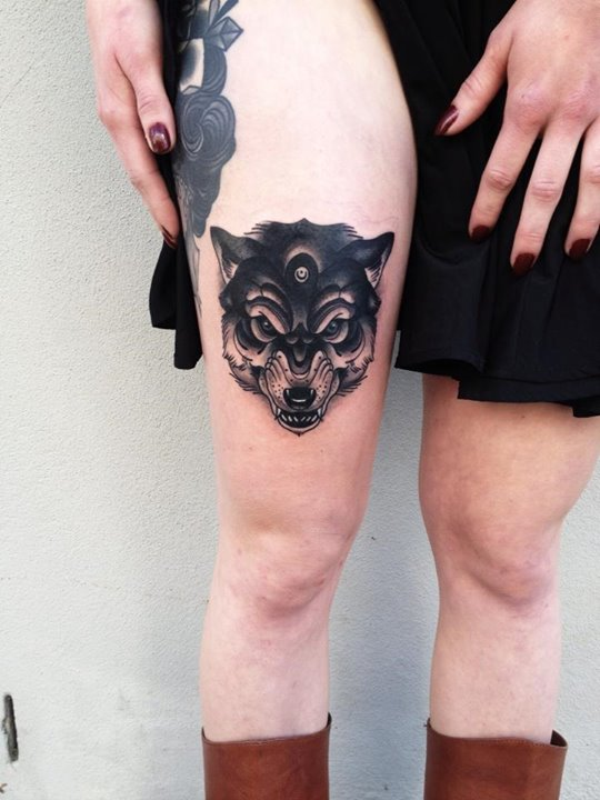 Black wolf head tattoo on the right thigh