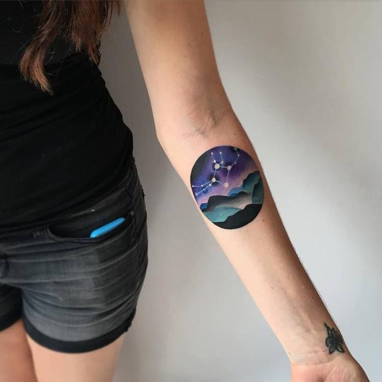 Circular landscape tattoo on the arm