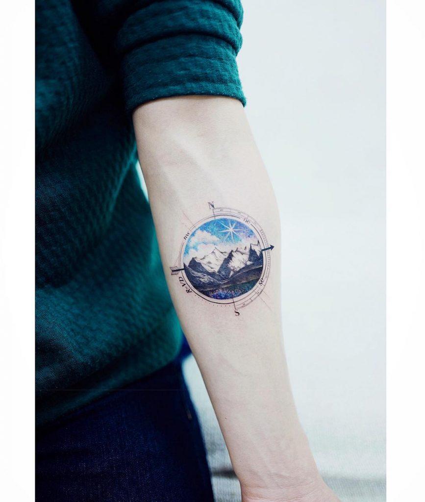 Circular mountain landscape tattoo and a compass