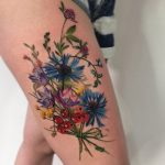 Colorful wildflowers tattoo on the thigh