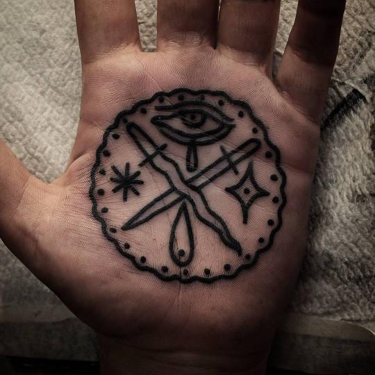 Crossed swords tattoo on palm