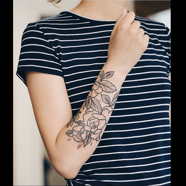 Delicate black outline tattoo on the right forearm