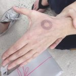 Dotted circle tattoo on the hand