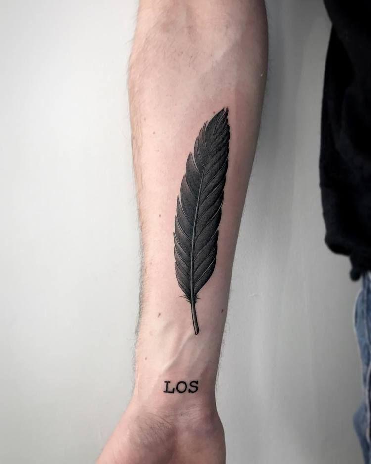 Fine black feather tattoo
