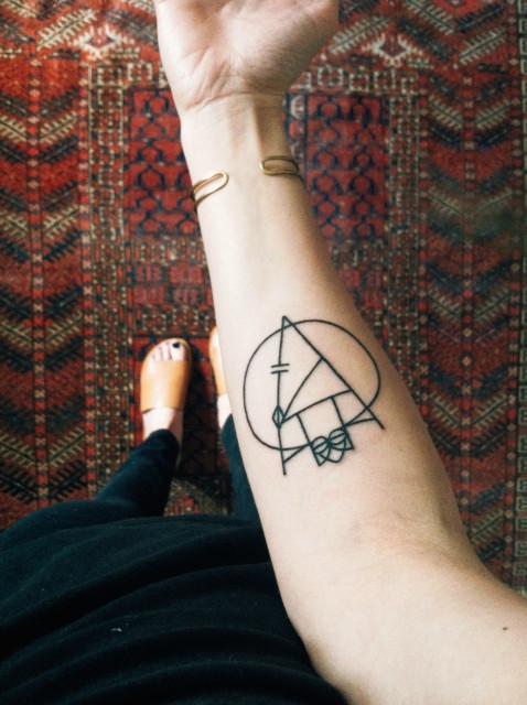 Geometric black linear tattoo on the forearm