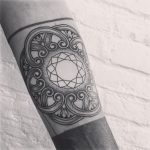 Geometric pattern tattoo on the left arm