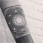 Geometric pattern tattoo on the left arm