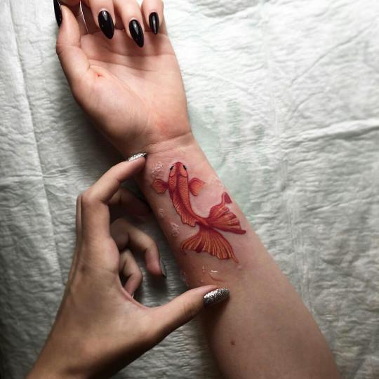 Gold fish tattoo on the wrist