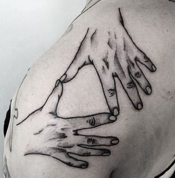 Hands tattoo on the shoulder
